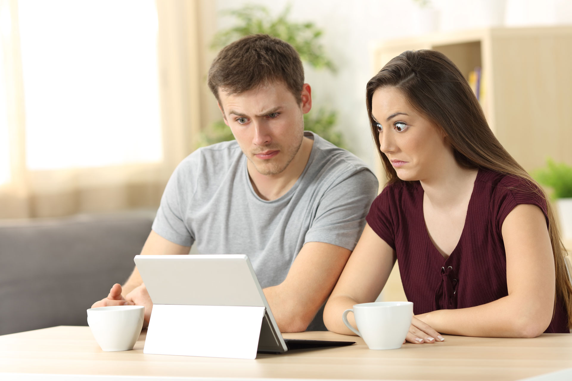 Confused couple looking at a tablet screen